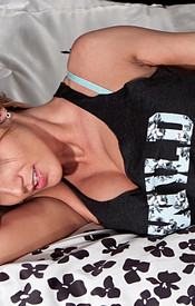 Busty Nikki On The Bed With A Loose Tank Top On And Showing Off The Curves Of Her Boobs - Picture 1